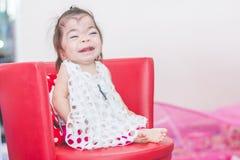 De speciale zoete Aziatische zitting van het babymeisje op stoel stock foto