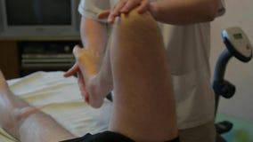 De specialist maakt tot een massage aan gehandicapte persoon stock videobeelden
