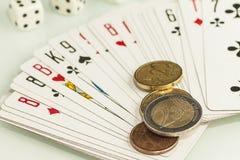 De speelkaarten en dobbelen op een witte achtergrond met muntstukken Stock Afbeeldingen