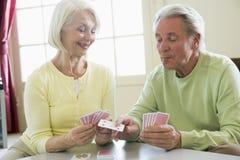 De speelkaarten van het paar in woonkamer het glimlachen Stock Foto