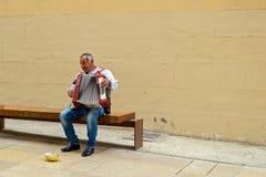 De speelmelodieën van de straatmusicus met zijn oude harmonika stock afbeeldingen