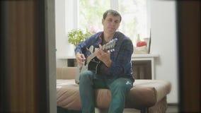 De speelmuziek van de mensengitarist door houten akoestische gitaar Mens die Akoestische Gitaar dicht omhoog langzame geanimeerde stock footage