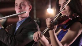 De speelmuziek van de twee mensenmusicus Een mooi brunette in een blauwe kleding speelt de viool, en de kerel in het jasje en het stock footage