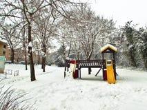 De speelplaats van jonge geitjes met gele en rode die dia in sneeuw wordt behandeld stock afbeeldingen