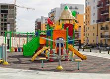 De speelplaats van kinderen met dia's en schommeling in de binnenplaats van woningbouw stock fotografie