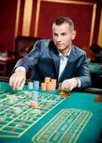 De speelroulette van de gokker bij het casino royalty-vrije stock afbeelding