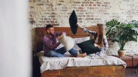 De speelse jonge paar knappe gebaarde mens en het slanke mooie meisje fighing hoofdkussens op tweepersoonsbed, die pret hebben en stock video