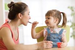 De speelse lepel die van het babymeisje haar moeder voeden royalty-vrije stock fotografie
