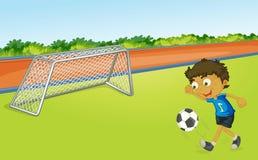 De speelvoetbal van de jongen Stock Foto's