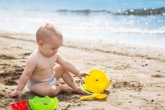 de speelzitting van de babyjongen op het strand Royalty-vrije Stock Afbeeldingen
