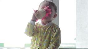De speelzitting van de babyjongen op het venster en het ruiken van een bloem Stock Afbeelding