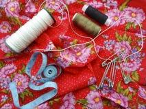 De spelden van garennaalden op rode stof Stock Foto