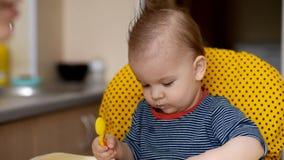 De spelen van één éénjarigenkind in de keuken met schotels stock video