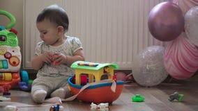 De spelen van de babypeuter met plastic groot schip bij haar verjaardag met roze impulsen stock videobeelden