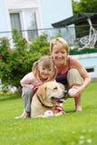 De spelen van de familie met een hond Stock Afbeelding