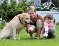 De spelen van de familie met een hond Royalty-vrije Stock Foto's