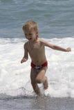 De spelen van de jongen bij de kust Stock Afbeeldingen