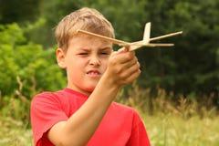 De spelen van de jongen met houten vliegtuig op aard stock foto's