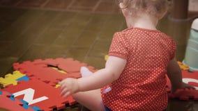 De spelen van het babymeisje met kleurrijk raadsel bekleden tegels thuis met brieven stock video