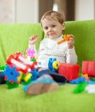 De spelen van het kind met speelgoed in huis Stock Foto