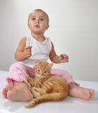 De spelen van het peuterkind met een kat stock fotografie