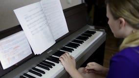 De spelen van het tienermeisje op het toetsenbord van de digitale piano stock video
