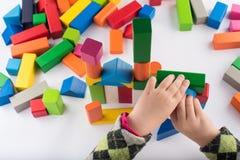 De spelen van het vier éénjarigenmeisje in de ontwerper Houten speelgoed, kleurrijke kinderen` s ontwerper op witte achtergrond,  royalty-vrije stock fotografie