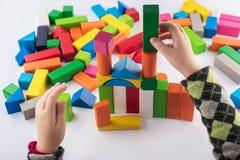 De spelen van het vier éénjarigenmeisje in de ontwerper Houten speelgoed, kleurrijke kinderen` s ontwerper op witte achtergrond,  royalty-vrije stock foto's