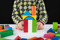 De spelen van het vier éénjarigenmeisje in de ontwerper op de lijst Houten speelgoed, kleurrijke kinderen` s ontwerper, zwarte ac royalty-vrije stock foto's