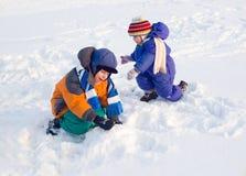 De spelen van kinderen aan sneeuw Royalty-vrije Stock Afbeeldingen