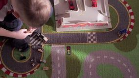 De spelen van weinig blondejongen met auto's op tapijt stock footage
