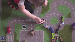 De spelen van weinig blondejongen met auto's op tapijt stock video