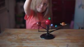 De spelen van weinig blondemeisje met de lay-out van het zonnestelsel stock video