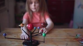 De spelen van weinig blondemeisje met de lay-out van het zonnestelsel stock videobeelden