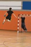 De speler die van het handbal met de bal springt Stock Afbeelding