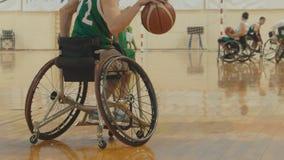 De speler die van het rolstoelbasketbal de bal druppelen snel tijdens opleiding van gehandicapte sportmannen stock afbeelding