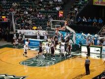 De speler dompelt basketbal als andere poging onder aan blok Stock Foto
