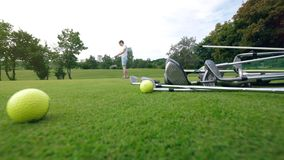 De speler gebruikt golfclub aan praktijkklappen op een cursus stock videobeelden