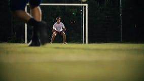 De speler schopte de bal, strevend naar het doel, maar de keeper raakte de bal stock videobeelden