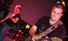 De speler van de gitaar het spelen op stadium Royalty-vrije Stock Afbeelding
