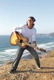 De speler van de gitaar op de rotsen Stock Foto's