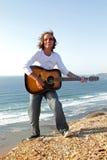 De speler van de gitaar op de rotsen Stock Foto