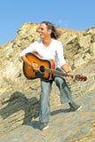 De speler van de gitaar op de rotsen Royalty-vrije Stock Fotografie