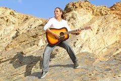 De speler van de gitaar op de rotsen Stock Afbeelding