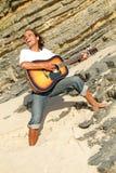 De speler van de gitaar op de rotsen Royalty-vrije Stock Afbeeldingen