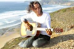 De speler van de gitaar op de rotsen Stock Afbeeldingen