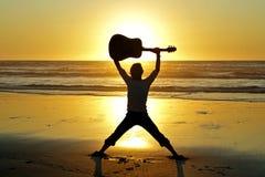 De speler van de gitaar op het strand Royalty-vrije Stock Afbeeldingen