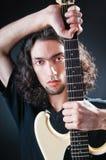 De speler van de gitaar tegen dark Stock Fotografie
