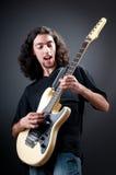 De speler van de gitaar tegen dark Stock Foto's