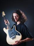 De speler van de gitaar tegen de zwarte Stock Foto